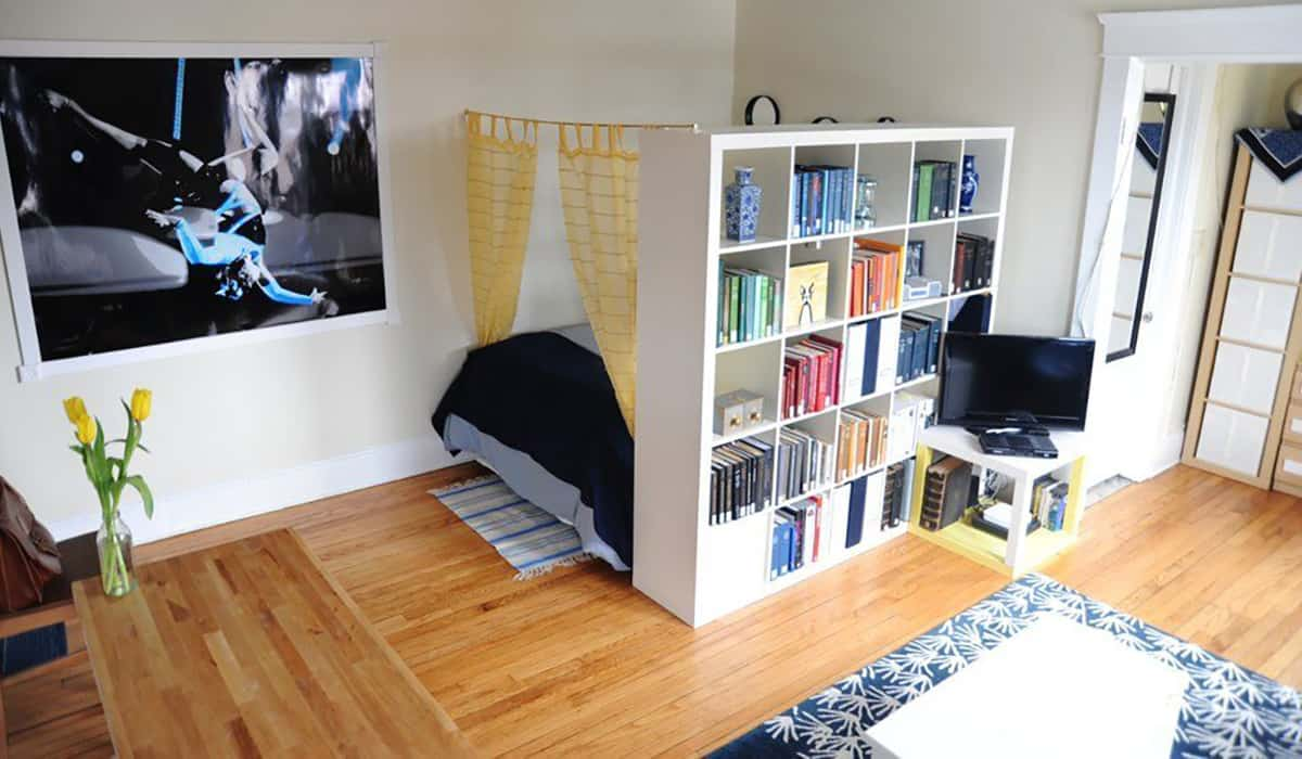 bookshelf divider used to create makeshift bedroom