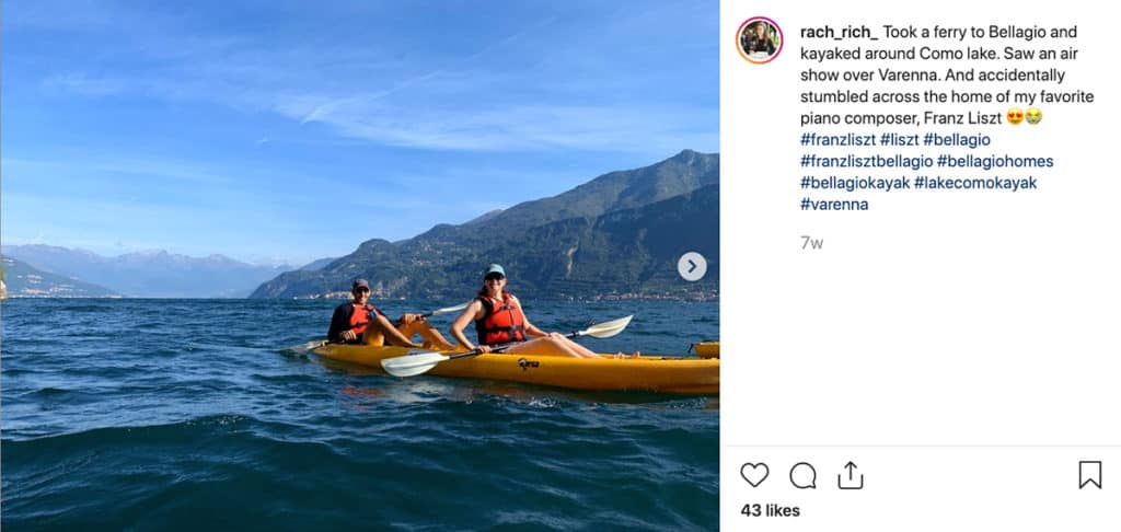 2 people paddling in a kayak on Como Lake with mountains behind them
