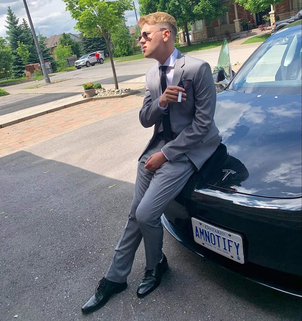 Aaron Maresky in a suit leaning against a car