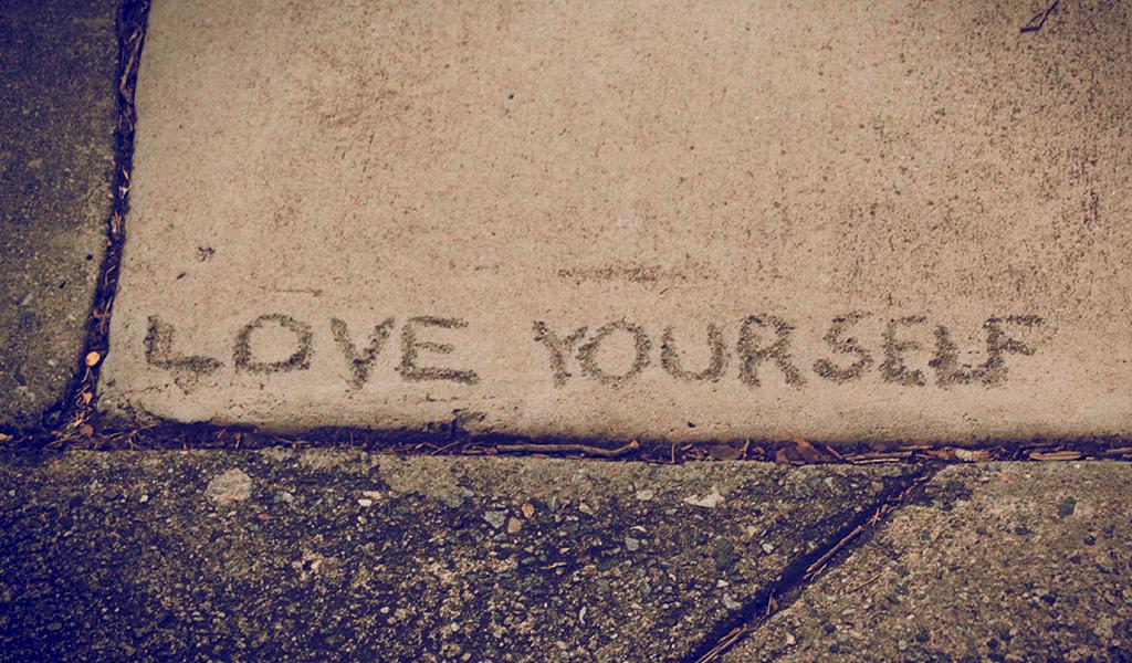 Love yourself written on sidewalk