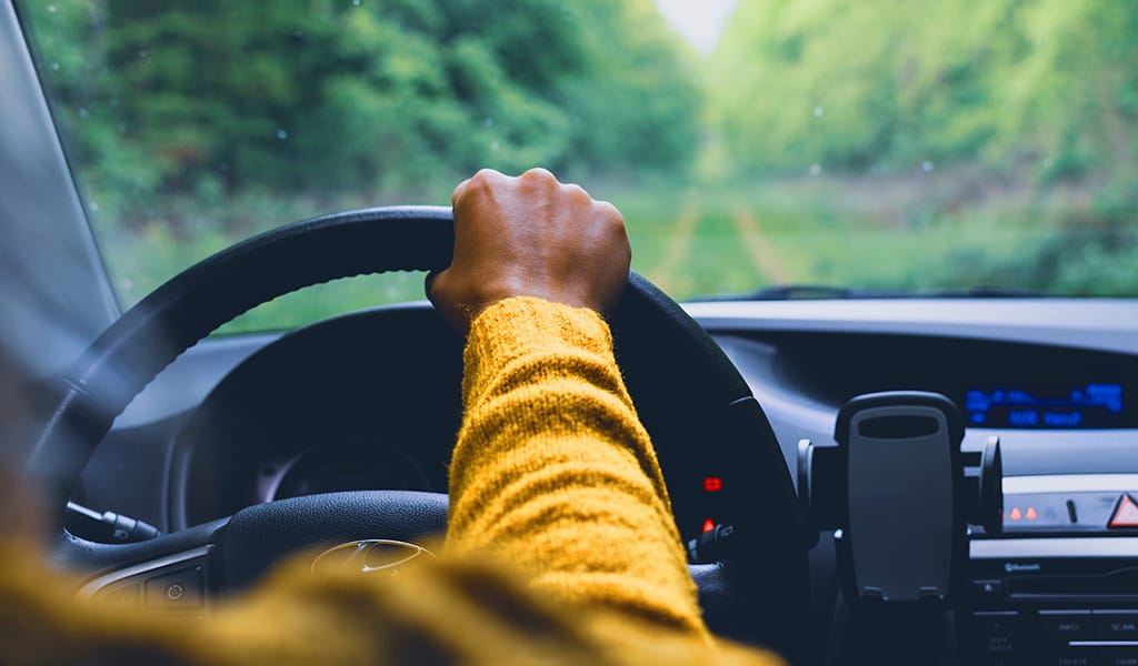 arm of man on wheel, driving car