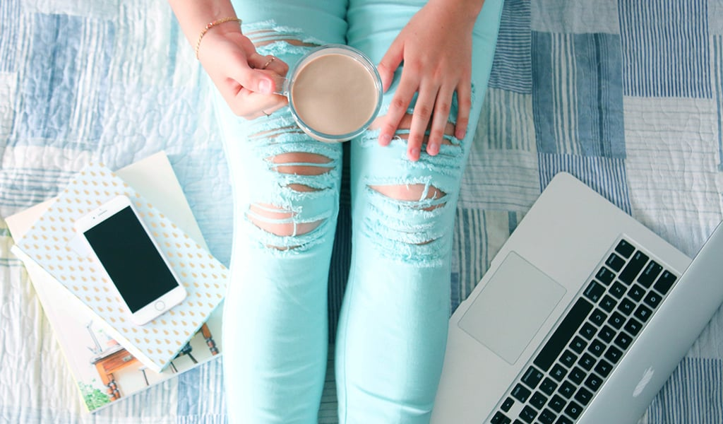 legs of woman and hands shown holding coffee mug next to phone, notebooks, and laptop