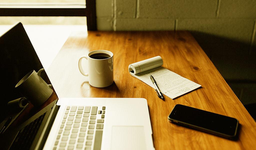 Laptop, mug, notebook, pen, and phone