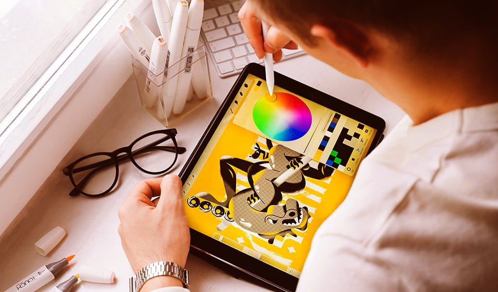 man doing graphic design on tablet