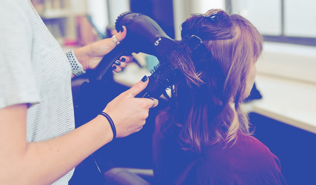 woman blowdrying another woman's hair