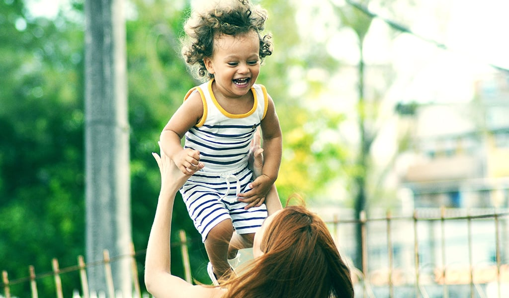back of young woman lifting up laughing toddler