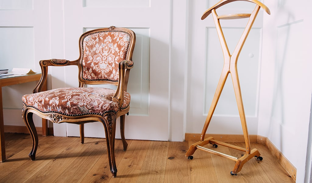 antique chair next to portable clothing rack