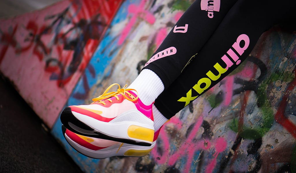 legs crossed, showing a pair of brightly colored athletic shoes, against a wall covered in graffiti