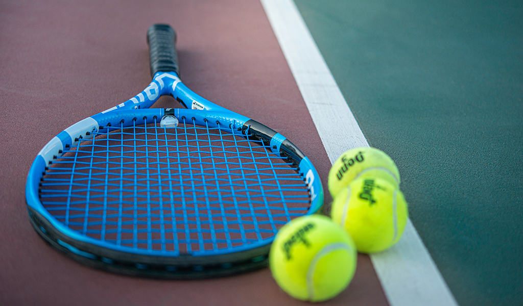 Blue and black tennis racket and 3 tennis balls laying on a tennis court