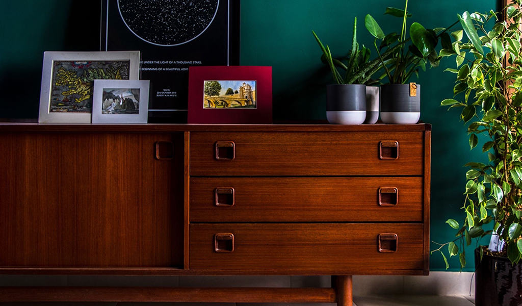 mid-century cherry-stained sideboard with decor on top, plant to the right
