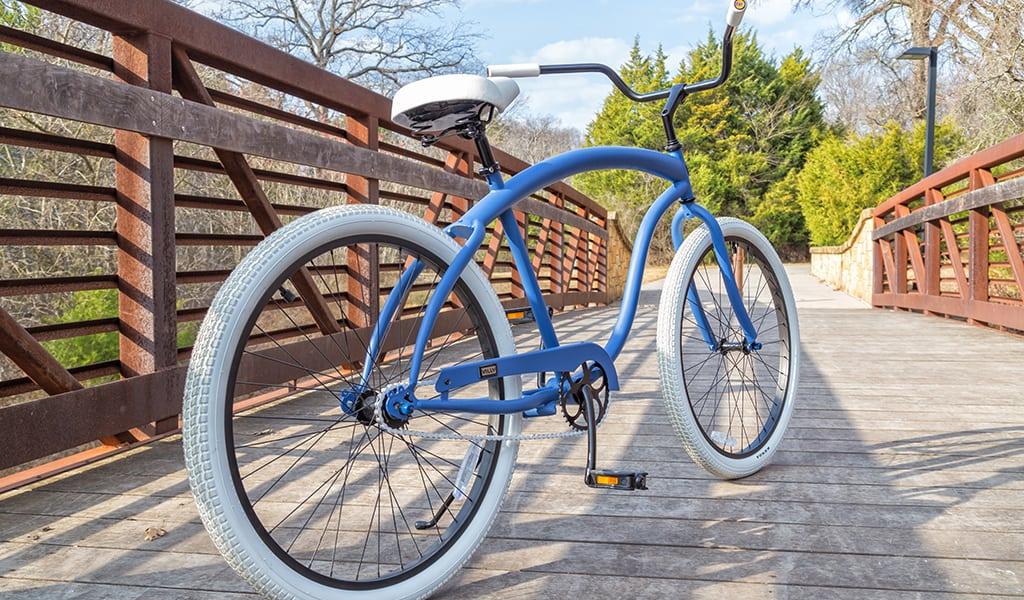 Blue cruiser bike parked on a bridge outside