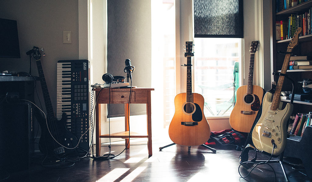multiple guitars, a keyboard, and a microphone in a home