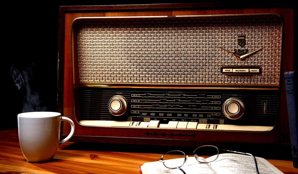 vintage radio on wooden table, with a coffee mug, glasses, and a book