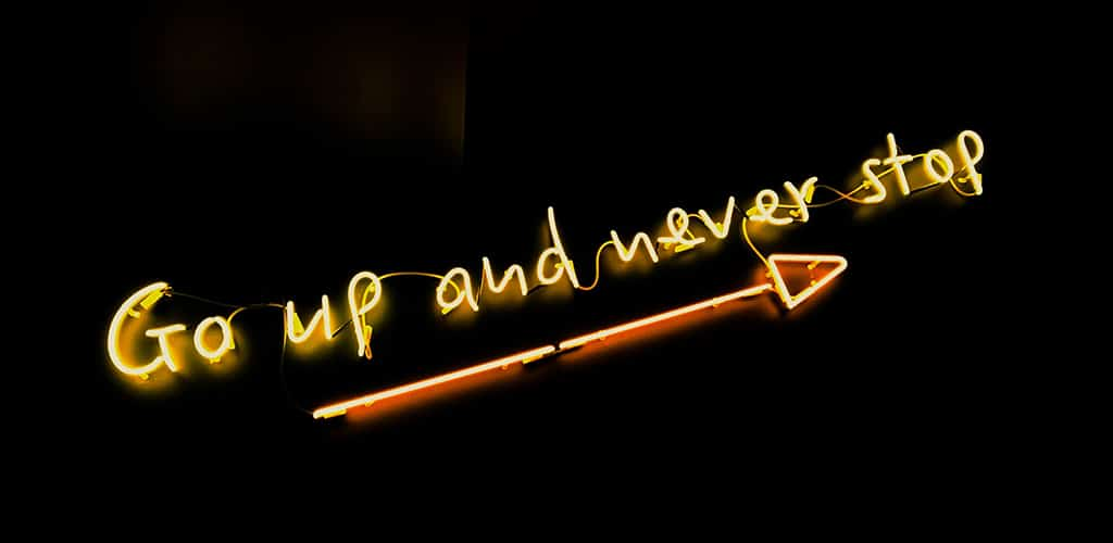 """electric sign, """"Go up and never stop"""" with an arrow angled up"""