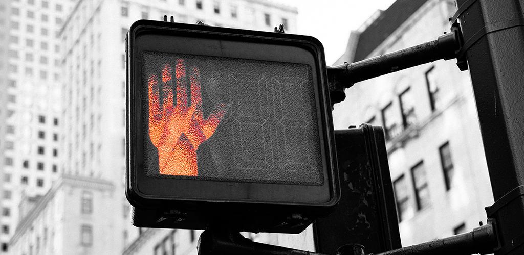 "crosswalk ""don't walk"" hand signal at city intersection"